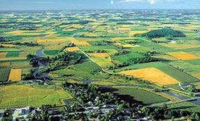 Aerial photograph of flat landscape with fields and a small village.