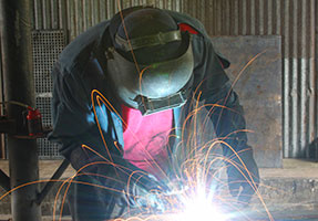 Photo of man welding with safety mask and sparks